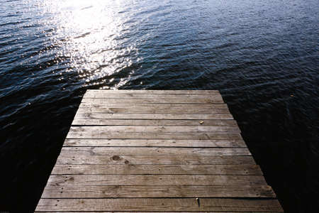 Wooden bridge on the lake in the sun