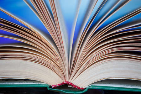 Pages of an unfolded book with a binding on a colorful background