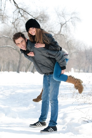 young couple having fun in the park, in winter holidays photo