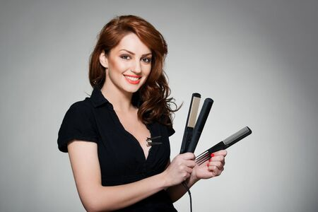 portrait of a young red hair woman, holding a comb and flat iron photo