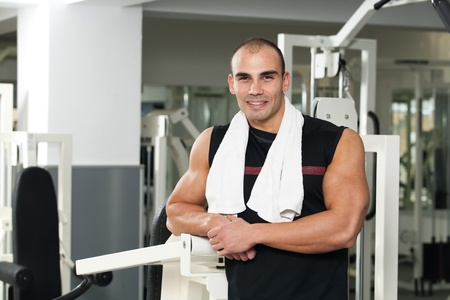 young caucasian bodybuilder in the gym smiling, with a towel around his neck photo