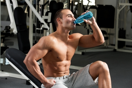 young caucasian bodybuilder in the gym, drinking a bottle water photo