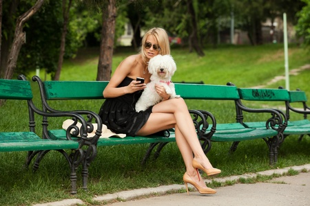 young fashion woman in the park with her dog, checking her phone photo