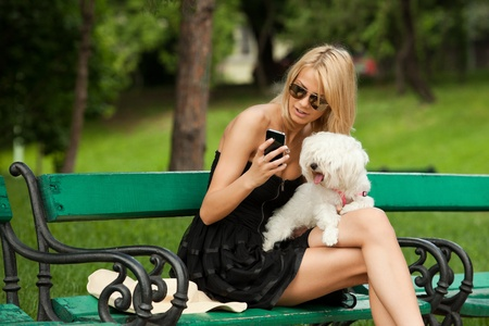 young fashion woman in the park with her dog, checking her phone