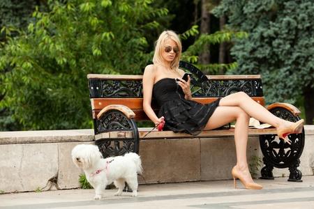 tacones negros: la mujer de moda joven en el parque con su perro, comprobando su teléfono