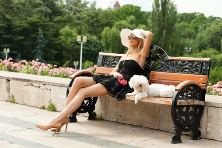 young fashion woman in the park with her dog, sitting on the bench photo