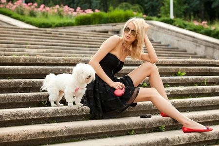 young fashion woman in the park with her dog photo