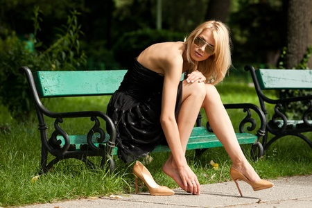 high park: young woman sitting on a bench, having a foot ache from her shoe Stock Photo