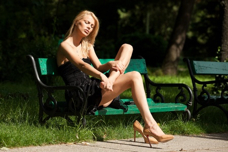 animal foot: young woman sitting on a bench, having a foot ache from her shoe Stock Photo