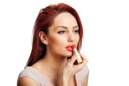 portrait of a beautiful young red head woman applying lipstick, isolated on white background photo