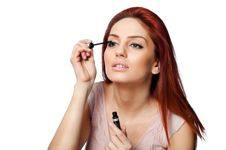 red head woman: portrait of a beautiful young red head woman applying mascara, isolated on white background