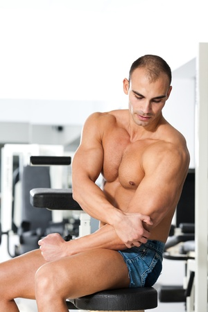 young caucasian bodybuilder having a elbow pain photo