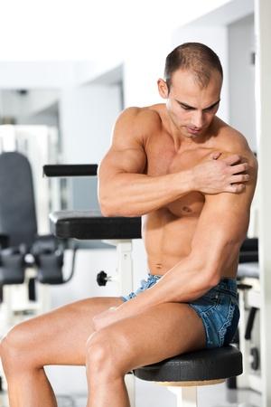 dolor muscular: joven culturista caucásico con un dolor en el hombro