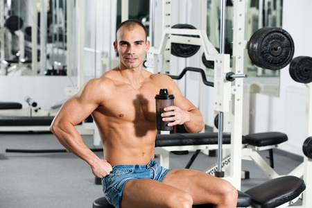 young caucasian bodybuilder in the gym, holding a protein shake photo