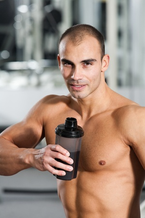young caucasian bodybuilder in the gym, drinking a protein shake photo