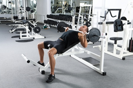 young bodybuilder training in the gym: chest - barbell incline bench press - wide grip  Stock Photo