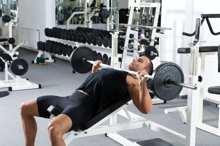 young bodybuilder training in the gym: chest - barbell incline bench press - wide grip  Reklamní fotografie