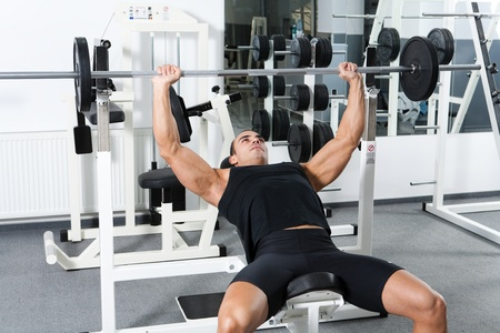 heavy weight: young bodybuilder training in the gym: chest - barbell incline bench press - wide grip  Stock Photo