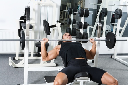 incline: young bodubuilder training in the gym: chest - barbell incline bench press - wide grip