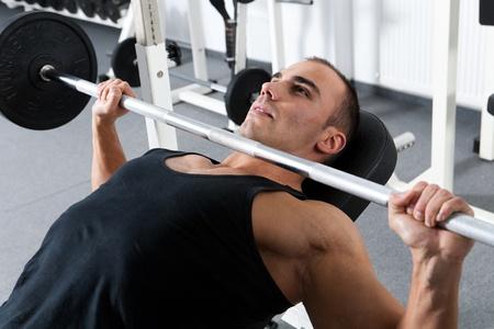 levantar peso: la formaci�n culturista joven en el gimnasio: pecho - barra en press de banca inclinado - agarre ancho
