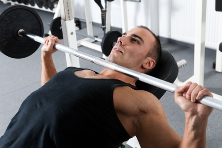 barbell: young bodybuilder training in the gym: chest - barbell incline bench press - wide grip  Stock Photo