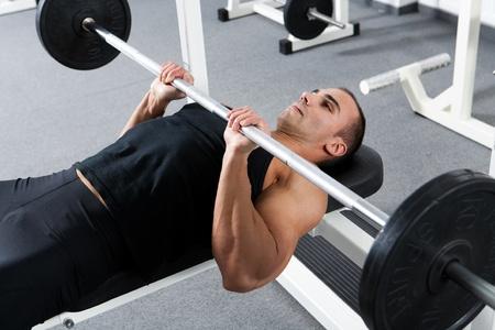 la formación culturista joven en el gimnasio: tríceps - agarre cerrado press de banca con barra Foto de archivo