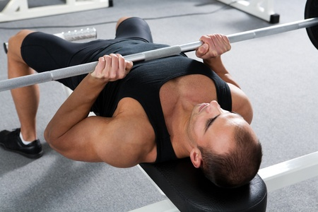barbell: young bodybuilder training in the gym: triceps - close grip barbell bench press