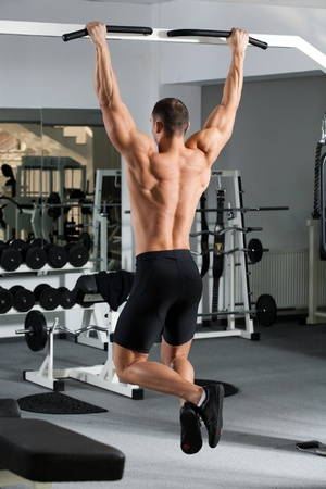young bodybuilder training in the gym: back - Wide-Grip Front Pull-Up  photo