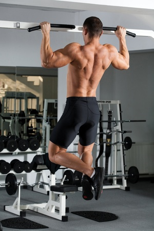 young bodybuilder training in the gym: back - Wide-Grip Front Pull-Up