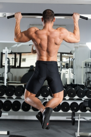 arm muscles: young bodybuilder training in the gym: back - Wide-Grip Front Pull-Up