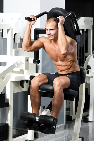young bodybuilder training in the gym: Abdominals - Crunch Machine, finish position Stock Photo - 12859805
