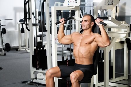 young bodybuilder training in the gym - machine shoulder press, start position Stock Photo