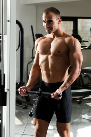 bicep: young bodybuilder training in the gym - standing biceps cable curl  Stock Photo
