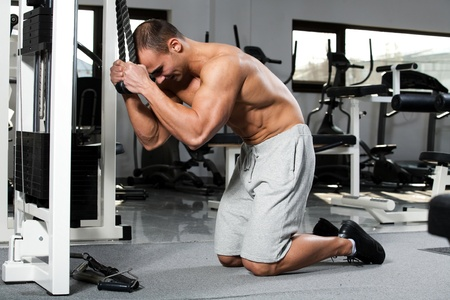 young bodybuilder training in the gym: Abdominals - Cable Crunch, start position