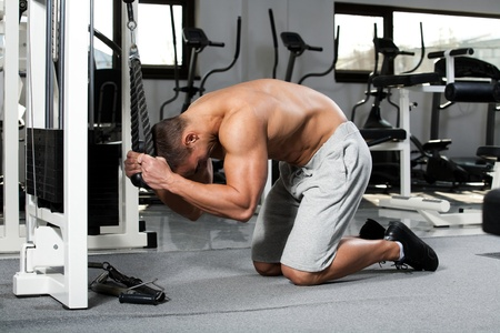 crunch: young bodybuilder training in the gym: Abdominals - Cable Crunch, finish position Stock Photo