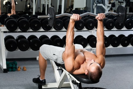 triceps: young bodybuilder training in the gym - triceps - lying E-Z curl bar press