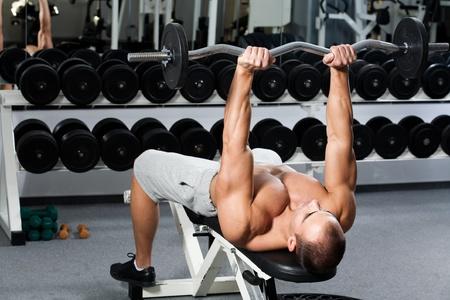 young bodybuilder training in the gym - triceps - lying E-Z curl bar press Reklamní fotografie - 12859839