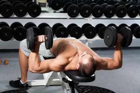 levantando pesas: la formaci�n culturista joven en el gimnasio: prensa de banca con mancuernas - la posici�n inicial