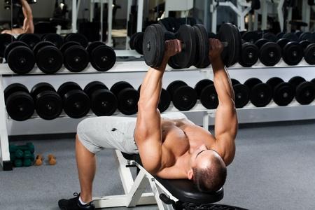 levantando pesas: la formaci�n culturista joven en el gimnasio: prensa de banca con mancuernas - posici�n final