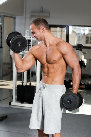 curls: young bodybuilder training in the gym - dumbbell alternate biceps curl