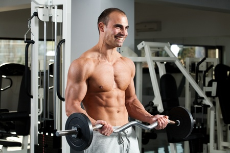 curls: young bodybuilder training in the gym - e-z bar biceps curl, start position Stock Photo