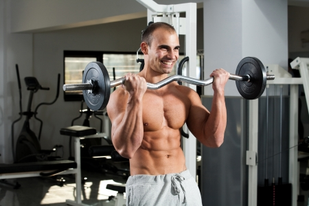 curls: young bodybuilder training in the gym - e-z bar biceps curl