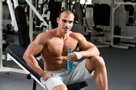 young caucasian bodybuilder in the gym, holding a bottle water photo