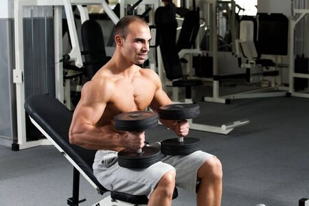young bodybuilder posing in the gym, with dumbbells in hands photo