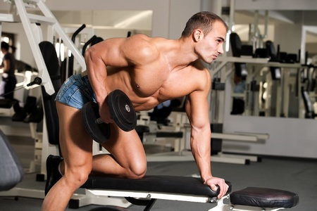dumbells: young bodybuilder training in the gym: back - dumbell rows -finish position