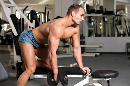 young bodybuilder training in the gym: back - dumbell rows - start position photo