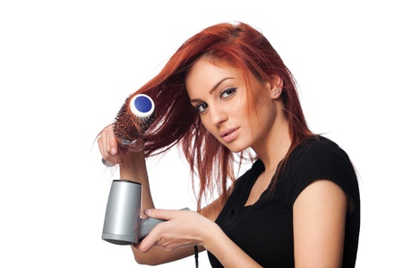 portrait of a beautiful young red head woman, drying her hair,  isolated on white background photo