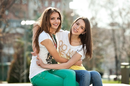 candid: two friends, happy, young women in the park