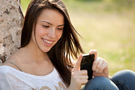happy young woman looking at her phone Stock Photo - 13225317