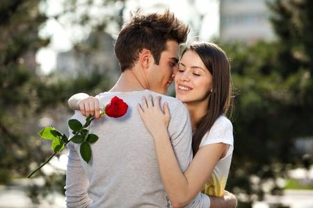 liefde: romantisch moment: jonge man die een roos aan zijn vriendin Stockfoto